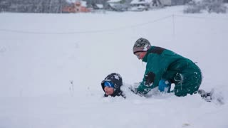 Two boys fighting while burying under snow. Two kids enjoying time outside in snow, snowballing and bury under piles of white cold snow.