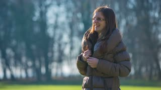 Undressing jacket on a sunny day. Warm day in winter, woman put down jacket while standing outside.