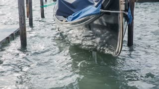 Venice gondola on rough wavy sea. Close up on gondola parked in pier while sea throwing it all around.