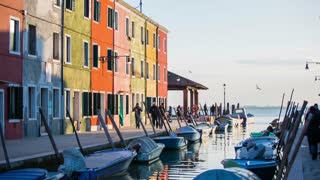VENICE, ITALY - FEBRUARY 2015: Beautiful Burano architecture at sunset. Wide shot of water canal running through buildings of Burano in different colors and built in lines.