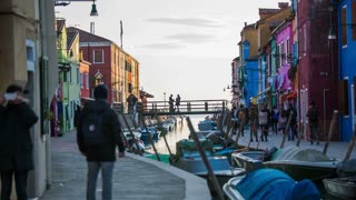 VENICE, ITALY - FEBRUARY 2015: Colorful buildings with water canal in Burano. Tourists visiting famous Burano canals with colorful facade buildings with historical stories.