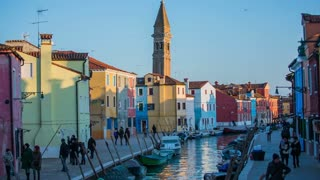 VENICE, ITALY - FEBRUARY 2015: Old town of Burano with leaned church tower. Long shot of Burano structures in different colors, people walking around, water canal running through and a leaned old church tower in background.