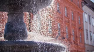 Water pouring from different layers on old fountain.Falling water from upper layers of old fountain in the middle of town on a sunny day.