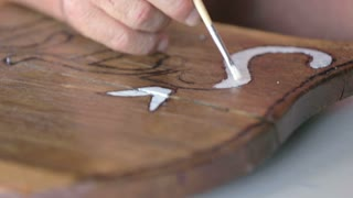 White word letters on wooden plank. Close up old hand drawing with white color brush on wooden plank.