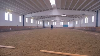 Wide Shot of Black Robe Person Riding Horse in Big Hall