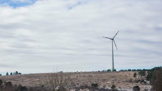 Wide shot of spinning wind turbine. Turning wind turbine on windy day producing electricity for locals.