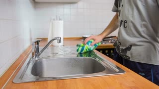 Wiping around kitchen sink with rag. Close up of male person with green rag wiping water around kitchen sink after cleaning dishes.
