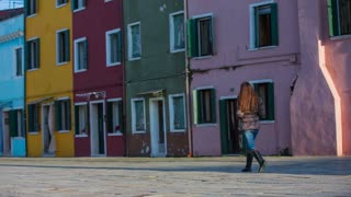 Woman alone in colorful street of Burano. Brown hair woman walking around Burano in Venetian Lagoon, enjoying time of colorful architecture on a sunny day.