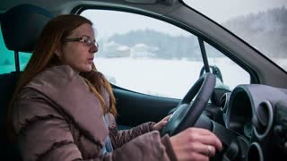 Woman driving car in snow. Female person in jacket steering wheel with view through side window of snowy countryside.