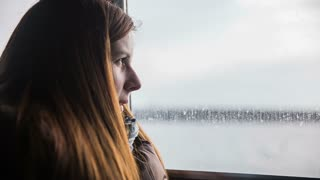 Woman face watching sea waves and smiling. Calm woman in warm clothes by a window on sea boat looking through with view of sea and ashore far away on a sunny day. Inside the cabin view.
