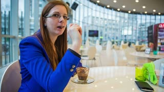 Woman flirting with camera in cafe. Medium shot of attractive female person in beautiful blue elegant jacket sitting in cafe eating hot chocolate dessert and smiling to camera.