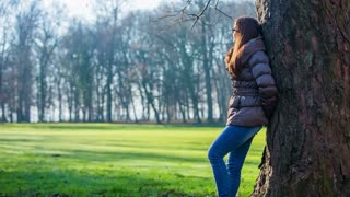 Woman in jacket resting leaning on tree. Person in forest park with green lawn in the middle leaning on tree, dressed in jacket because of cold weather.