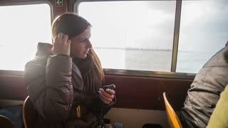 Woman plug headphones in ears while traveling. Medium shot of attractive woman travel on taxi cab  boat and listening to music. Cruising on ship with big windows with view on seascape and sun shining in background.