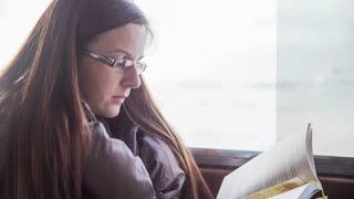 Woman read book on ship. Close up of woman interested in reading book while cruising on sea with taxi ship traveling to tourism location on a sunny day.