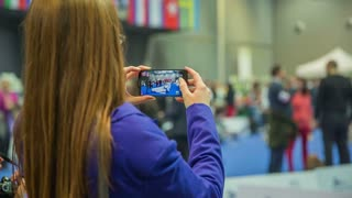 Woman recording event with smartphone. Female person with long brown hair and blue jacket watching dog show and video recording with big smartphone cellphone.