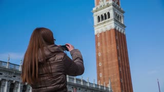 Woman taking picture of Piazza San Marco tower. Medium shot of brown hair person from behind taking photograph with smartphone of the famous Venice tower Piazza San Marco on a lovely sunny day.