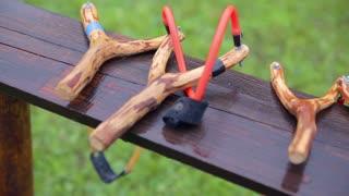 Wooden slingshots panning over close up. Professional made slingshot for competition waiting on desk.