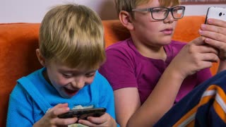 Young brothers playing with smartphones. Brothers in living room enjoying on sofa playing games on smartphones. Jib shot of kids using technology toys.