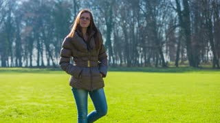 Young girl posing in nature. Attractive woman in warm clothes standing on big green lawn on a sunny day.