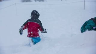 Young kid fighting with brother in snow. Two brothers in snow having fun fighting while older brother just throws kid in to snow over shoulder.