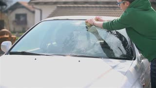 Young Man Cleaning Windshield With Sponge