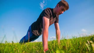 Young Man Doing Push-ups Wide Slow Motion. Low angle with grass in front and teenager doing push-up exercise outside.