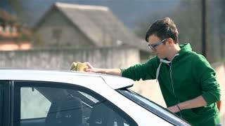 Young Man in Green Sweater Washing Car
