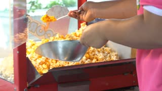4K, A static shot of a commercial popcorn machine. Mixing by human hand