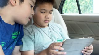 4K, Aisan child playing over tablet pc while family driving to vacation