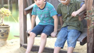 4k, Asian children sitting on swing chair outdoor