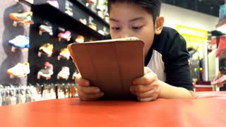 4K, Asian cute boy rest on floor and playing with tablet pc in shopping mall