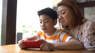 4K ,Happy asian boy and his mom playing games on smart phone