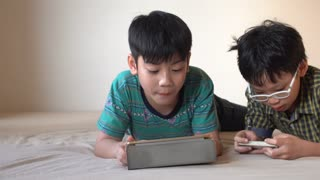 4K, Happy asian boy playing online games on tablet computer and smart phone .