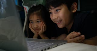 4K Happy asian child looking at computer under the table at home