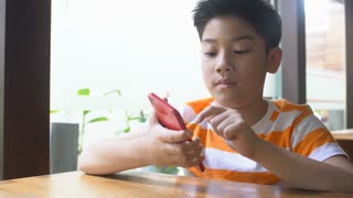 4k, Little asian cute boy is playing games on smart phone