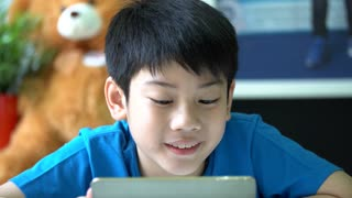 4k, Young asian boy browsing the internet on a digital tablet at home.