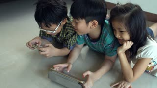 4K, Young asian child playing online games on tablet computer and smart phone .
