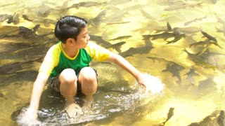 4K ,Young asian cute boy sit and play in the river .