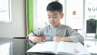 An asian boy doing his homework
