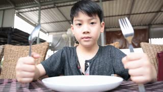 Angry asian child waiting food for launch .