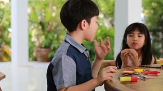 Asian boy and girl playing with slice of bread at home