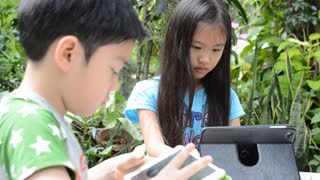 Asian boy and girls with a tablet computer in the garden.