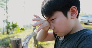 Asian boy crying in garden