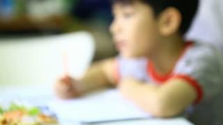 Asian boy doing homework at home .