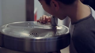 Asian Boy drinking at indoor water fountain
