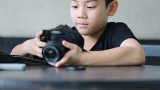 Asian boy looking and shoot with DSLR camera