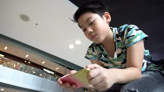 Asian boy playing phone in mall.