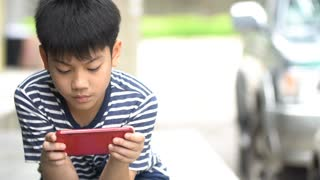 Asian boy using smart cell phone near the road ,Bangkok Thailand