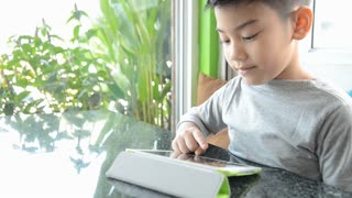 Asian boy with a tablet computer in the living room.