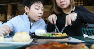 Asian boy with mother enjoy eating food at home